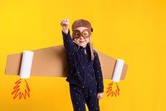 Frihet flickan som spelar för att vara flygplanpiloten, rolig liten flicka med flygarelocket och exponeringsglas, bär vingar som  Royaltyfria Foton