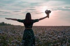 Frihet Kvinna med öppna armar och en bukett av blommor på solnedgången på en blommaäng royaltyfria bilder