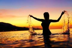 Frihet njutning Kvinna i havet på solnedgången Lycka sunt L arkivfoton