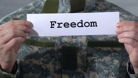 Frihet som är skriftlig på papper i händer av den manliga soldaten, frigörare av krigfångar stock video