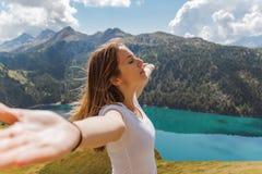 Frihetsbegrepp av en ung kvinna med hennes lyftta armar tycka om den nya luften och solen arkivbilder