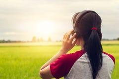 Frihetskvinna som utomhus tycker om musik med hörlurar arkivbild