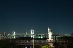 Frihetstaty på Odaiba med regnbågebron i bakgrund Tokyo Royaltyfri Bild