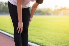 Friidrottkvinnalöpare som har ett knä att smärta och skada, når att ha kört som är utomhus- fotografering för bildbyråer