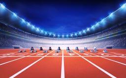 Friidrottstadion med loppspåret med främre sikt för startgrop Royaltyfri Bild