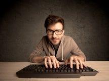 Friki del ordenador que mecanografía en el teclado Fotos de archivo libres de regalías