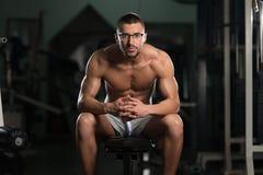 Friki joven atractivo que descansa en el ejercicio de Afther del gimnasio Imagen de archivo libre de regalías