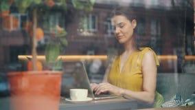 Frilans- arbeta för ung kvinna med bärbara datorn i kafét som skriver att le på tabellen lager videofilmer