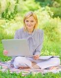 Frilans- arbete f?r aff?rsdam utomhus Bliven lyckad freelancer Kvinnan med b?rbara datorn sitter p? filtgr?s?ng Direktanslutet arkivfoton