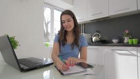 Frilans- arbete, lycklig ung kvinna som arbetar på bärbar datordatoren, medan laga mat i kök stock video