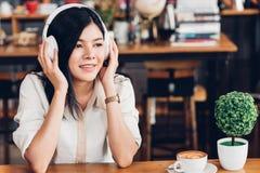 Frilans- kvinna för livsstil honom som använder lyssnande musik för hörlurar under att arbeta på bärbar datordatoren royaltyfri fotografi
