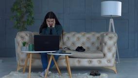 Frilans- kvinna på soffalidandehuvudvärk hemma stock video