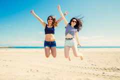 Frinds drôles de fille sautant sur la plage Photographie stock