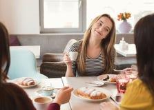 Frinds femelles heureux buvant du café et causant au café Image libre de droits