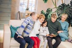 Frinedly uitgebreide familie het letten op foto's van tablet stock afbeeldingen
