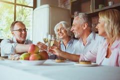 Frineds âgés gais buvant du champagne à la maison Images stock