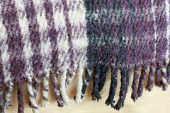 Fringe from plaid Mexican blanket. A warm, thick Mexican blanket made of cotton. Colors are shades of purple and off-white.  Fringed edge is visible Royalty Free Stock Images