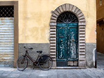 Fringed door and bike in Lucca Royalty Free Stock Image