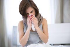 Frio travado mulher Sneezing no tecido Fotografia de Stock