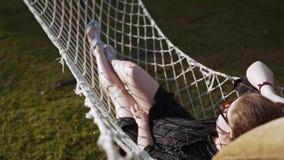 Frios da mulher na rede no por do sol, as férias e o relaxamento, a natureza e a recreação vídeos de arquivo