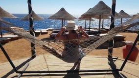 Frios na rede na praia, férias da mulher no mar, relaxando na praia, o mar e a recreação, a areia e o azul filme