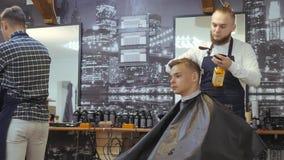 Frisör för män _ En ung grabb får en frisyr- och håromsorg från en skäggig man med hår som binds till hans huvud stock video