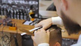 Frisör för män _ En ung grabb får en frisyr- och håromsorgservice från en skäggig man med ett hår som binds på lager videofilmer