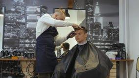 Frisör för män _ En ung grabb får en frisyr- och håromsorgservice från en skäggig man med ett hår som binds på stock video