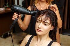 Frisör och klient i salongen, skönhetsalong och håromsorg royaltyfri fotografi