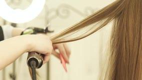 Frisör som använder den hårtång och hårkammen för hairstyling i skönhetsalong Slut upp frisören som in rätar ut långt hår stock video