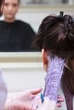 Frisör som applicerar den kvinnliga kunden för färg på salongen som gör hårfärg fotografering för bildbyråer