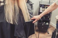 Frisör som gör en frisyr för klient arkivbild