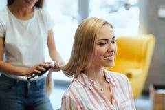 Frisör som gör frisyr för kvinnor i friseringsalong royaltyfri foto