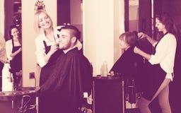 Frisör som gör frisyren arkivfoto