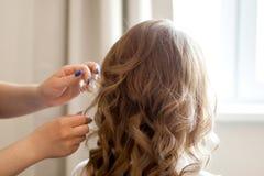 Frisör som gör lockig frisyr, skönhetsalong royaltyfria foton