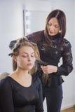 Frisör som rätar ut det långa bruna håret Royaltyfri Fotografi