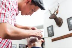 Frisör som rakar med den raka rakkniven fotografering för bildbyråer