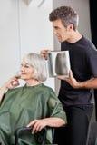 Frisör som visar färdig frisyr till kunden royaltyfria foton