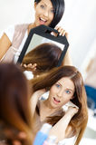 Frisör som visar frisyren av klienten i spegel royaltyfri fotografi