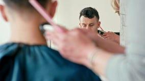 Frisör Works med clipperen som gör frisyr för brunhårig man i frisersalong arkivfilmer