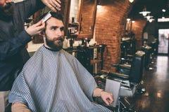 Frisören är bitande hår av hans kund Han gör, att mycket exakt och mjukt Kunden sitter i a royaltyfria bilder