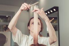 Frisören är bitande långt hår i hårsalong arkivfoton