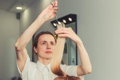 Frisören är bitande långt hår i hårsalong arkivfoto