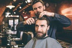 Frisören använder sax för bitande hår Han gör det som mycket är exakt Den Te kunden ser rättfram arkivfoto