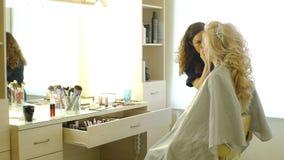 Frisören gör aftonfrisyrnärbild på blont hår av affärskvinnan i skönhetsalong stock video