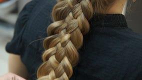 Frisören gör frisyrblondinflickan Hairstylingprocess stock video