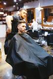 Frisören gör frisyren för en ung man Royaltyfri Fotografi