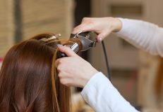 Frisören gör frisyrflickan med långt rött hår i en skönhetsalong arkivfoton
