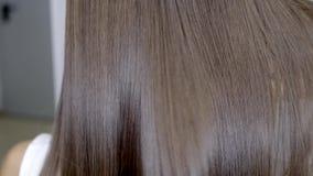 Frisören gör hårlamination i en skönhetsalong för en flicka med brunetthår arkivfilmer