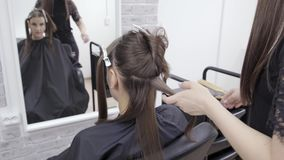 Frisören gör hårlamination i en skönhetsalong för en flicka med brunetthår Begrepp f?r h?romsorg lager videofilmer